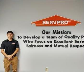 Latino brown skin male with black hair wearing a SERVPRO logo polo shirt