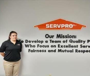 young white woman in black SERVPRO logo polo and khaki pants with the SERVPRO logo in background