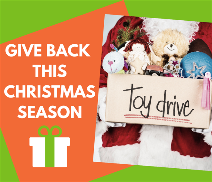 Santa Claus holding Toy Drive Box with toys inside with green back ground and orange box that says give back this Christmas