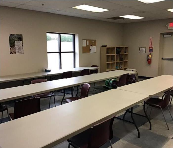 Cafeteria with 3 long tan tables and maroon chairs scooted in. Bulletin board and fire extinguisher on wall.