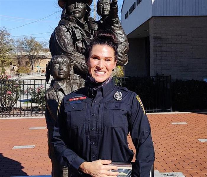 white female firefighter in blue uniform smiling with blue sky and statue behind her